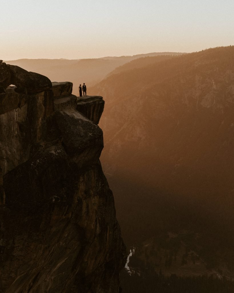 couple standing on diving board at taft point overlooking yosemite valley at sunset